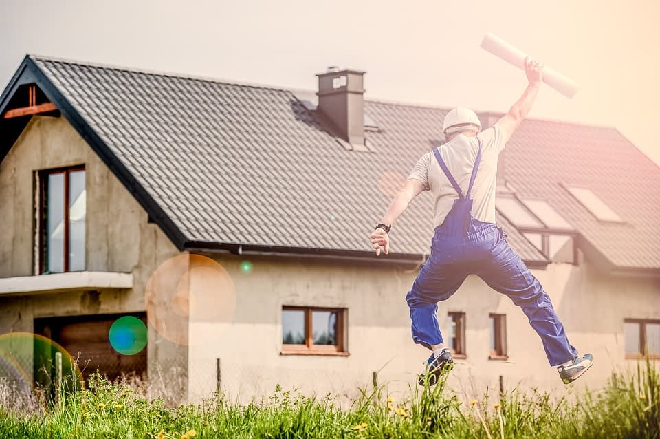 man jumping with house in background