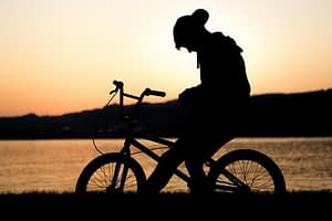 person on bicycle near lake